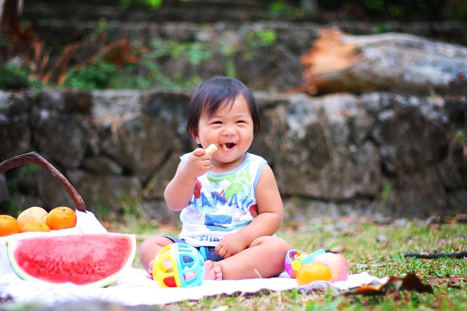 Kleinkind, ca. 1 Jahr, sitzt auf Decke und isst, Spielzeug, Wassermelone, Kind lacht