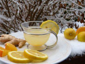 Teller, Scheiben von Zitrone, Ingerwurzel, Teeglas mit milchiger Flüssigkeit