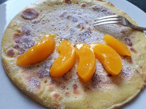 Pfannkuchen mit Puderzucker bestäubt, Schnitze von Pfirsichen, goldgelb