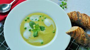 Suppenteller, nah, gefüllt mit grüner Suppe, Pfefferminzblatt als Dekoration, dazu weiße Sahneflecken und einzelne Erbsen