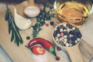 Brett mit Knoblauchzehe, Rosmarinzweig, Pfefferkörnern in einem Löffel, Chilischote