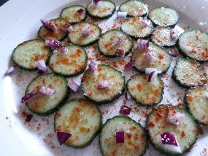 Gurken, rechts in Stäbe geschnitten, mit Pfeffer, Salz, Cayenne. Links in Scheiben, mit Gewürzen, zusätzliche Zwiebeln