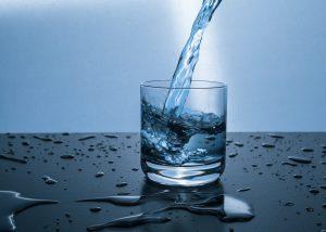 Glas, in das im Bogen Wasser gegossen wird, Tropfen, Kunstbild