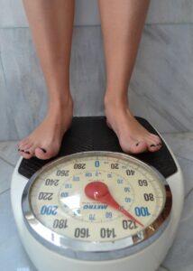 Waage, Zeiger steht auf fast 120 Kilo, Beine im Anschnitt, nur Füße zu sehen
