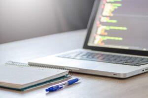 Tisch, Notebook, Block und Stift, alles nah, Monitor im Anschnitt, unscharfe Statistiken und Felder