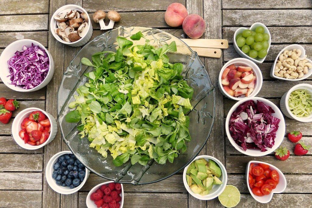 Glasschüssel mit Salat, umgeben von kleinen Schüsseln mit Erdbeeren, Pilzen, Trauben, Nüssen, Rotkraut, Tomaten, Weißkohl
